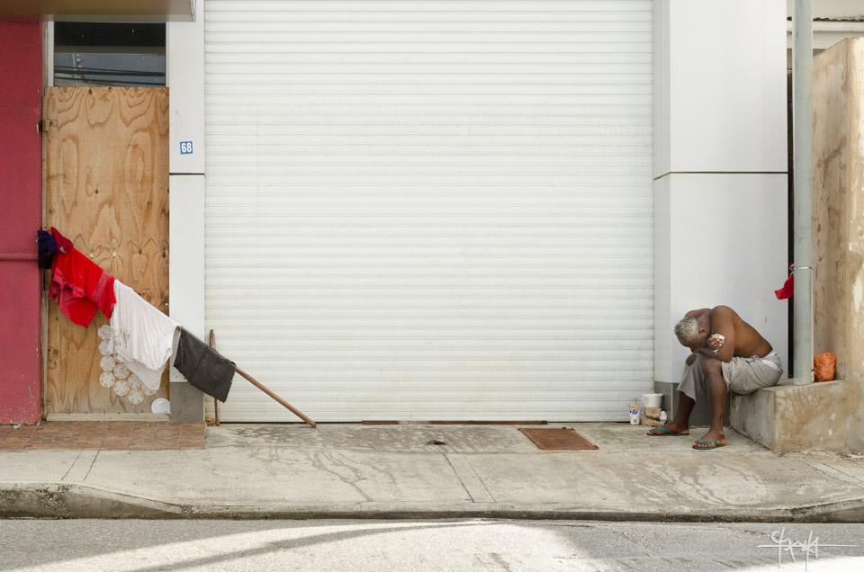 A street dweller, known as Bernard Smart, sits huddled, across from clothing hung along a wooden rod. January 3rd, 2015.