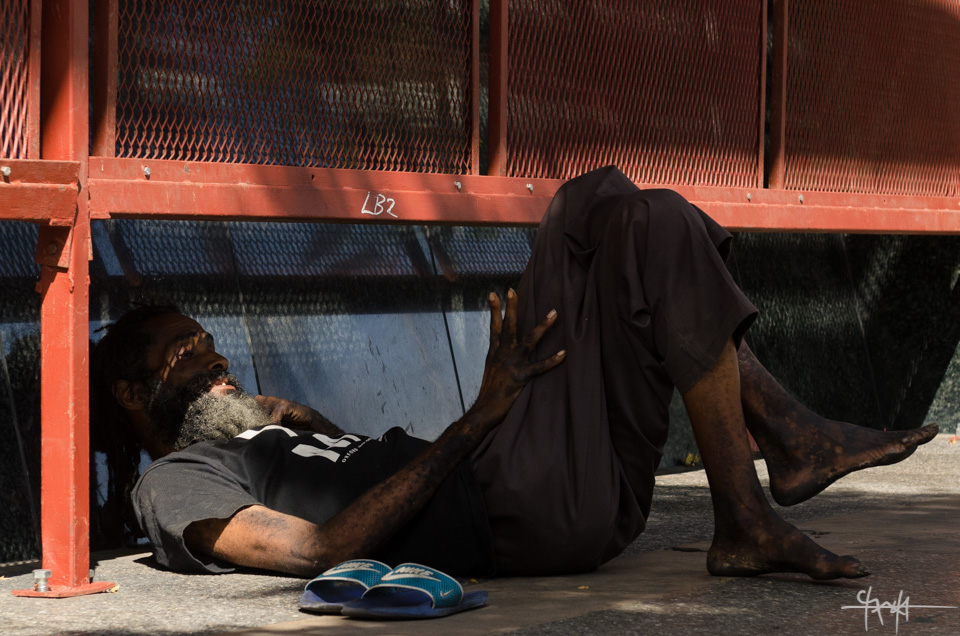 A homeless man chats with himself under the shade of a bank on Independence Square, Port of Spain. February 17th, 2015.