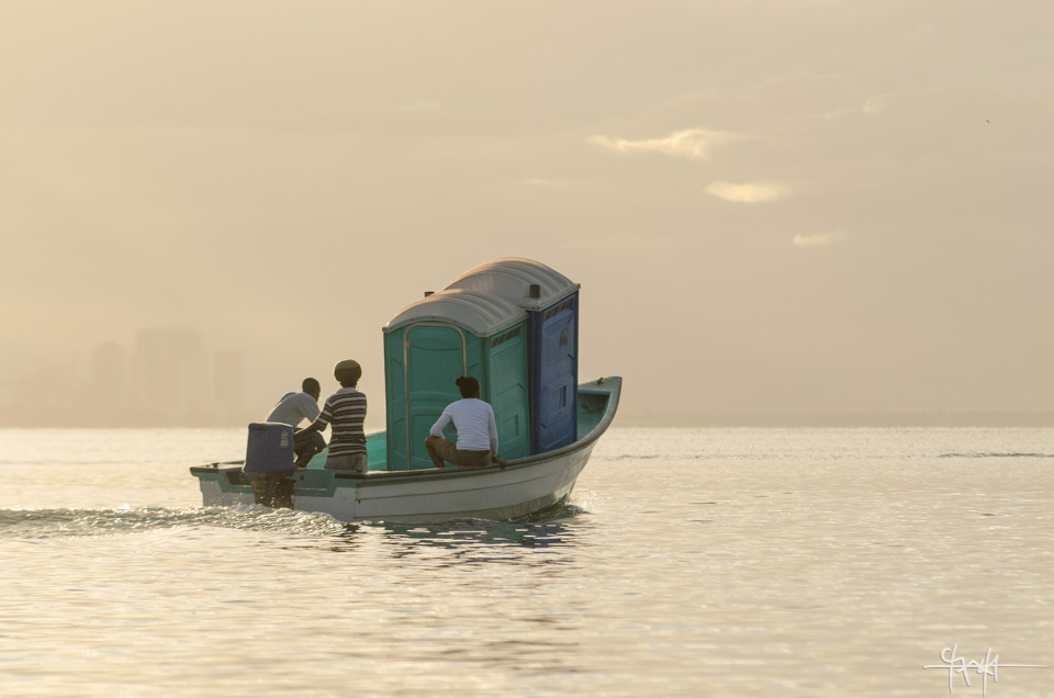 Image Caption: Men transport portable toilets via a pirogue. Chaguaramas - March 1st, 2015.—Click to read this article.