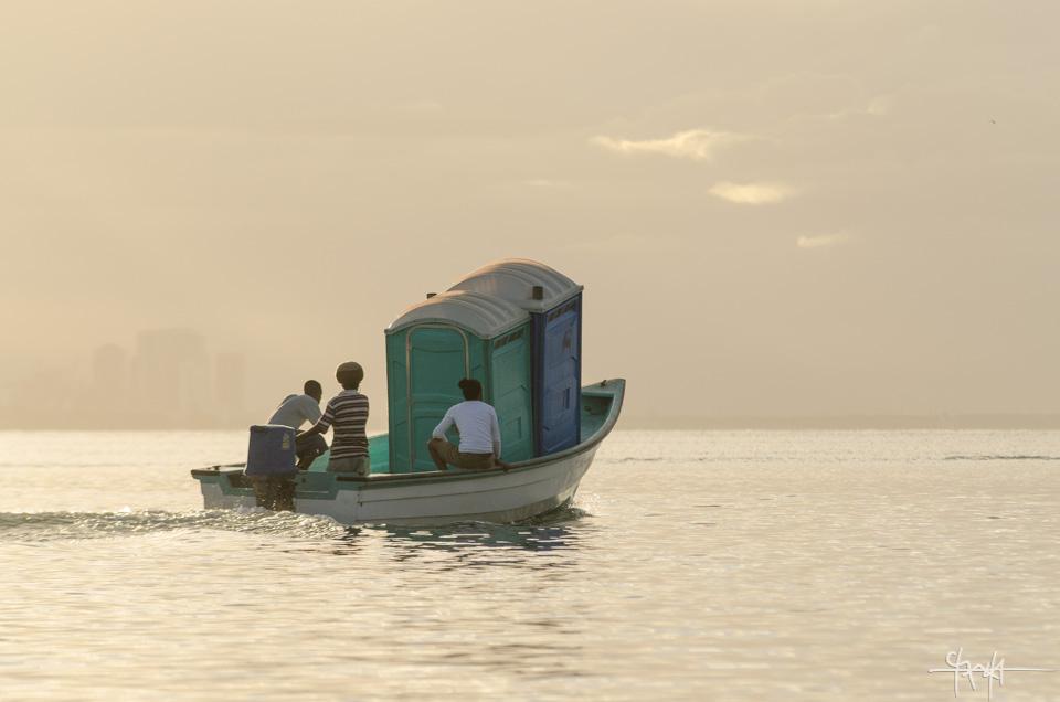 Men transport portable toilets via a pirogue. Chaguaramas - March 1st, 2015.