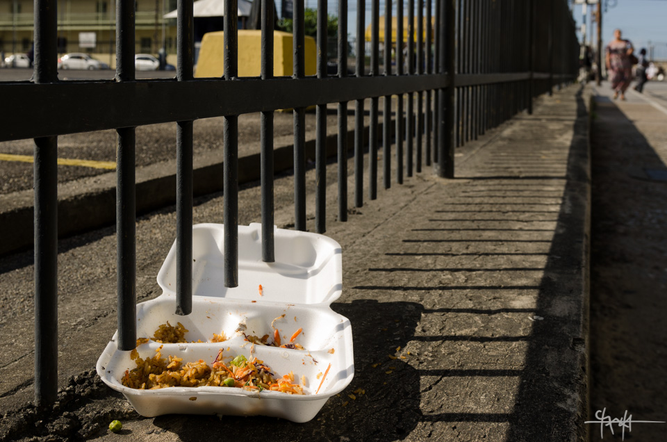 Image Caption: A discarded food box sits on a low wall on lower Chacon Street, Port of Spain - July 11th, 2015.—Click to read this article.
