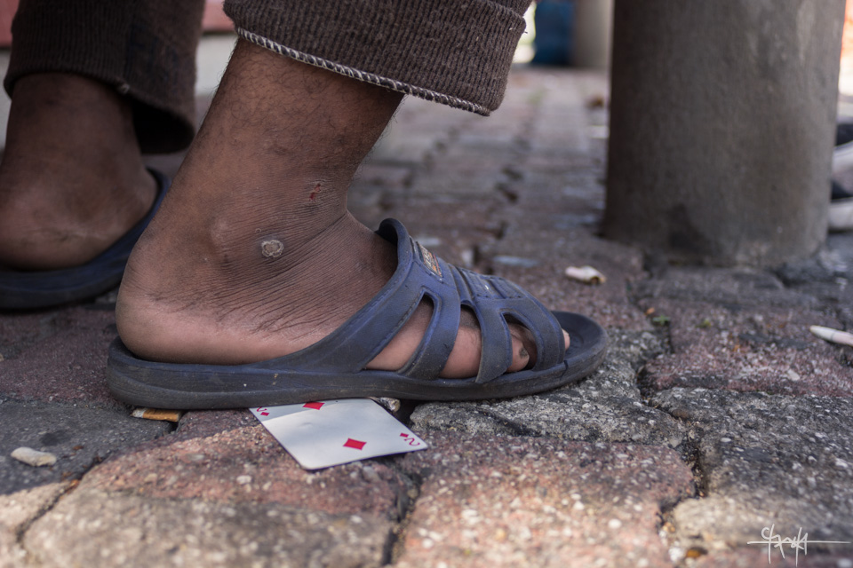 Image Caption: A sandalled foot steps on a playing cards on Independence Square, Port of Spain. October 17th, 2015.—Click to read this article.