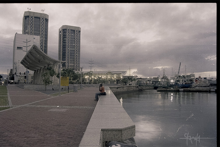 Image Caption: View overlooking the ferry port and the Breakfast Shed of Port of Spain, with the twin towers of Central Bank of Trinidad and Tobago in the background. January 2011.—Click to read this article.