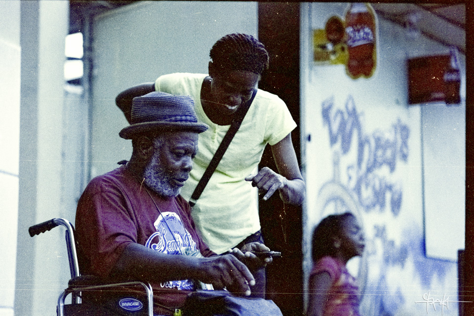 A smiling lady points at something on a cellphone held by an older man displaying a possible expression of concentration. In the background is a younger girl. 'Wheels and Caro' snackette, Charlotte Street, Port of Spain. February 9th, 2016 - Kodak ProImage 100.
