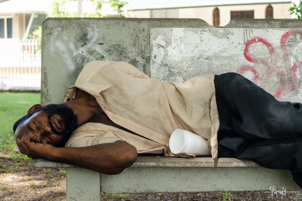 Image Caption: A man in worn clothing sleeps on a concrete bench in Victoria Square, Port of Spain. 30th July, 2016. (Shaun Rambaran / Forge Business Imagery)—Click to read this article.