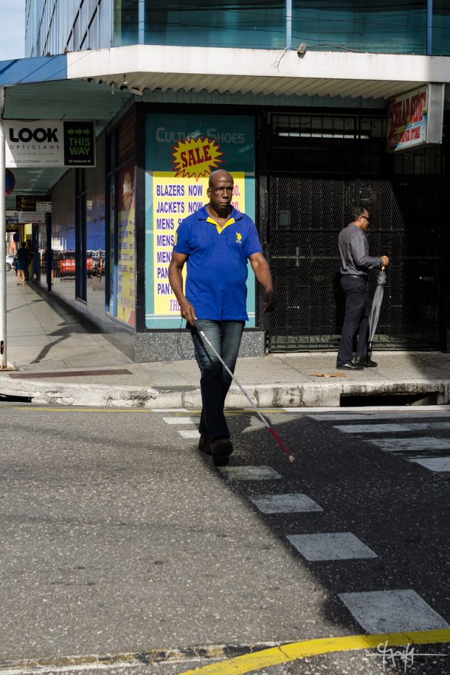 A visually-impaired man crosses the street. 5th October, 2016.