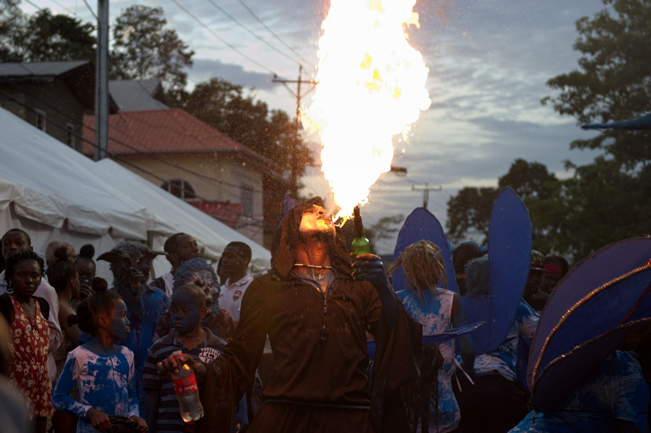 Image Caption: A fire-breathing, blue devil spits a flame into the air. Piccadilly Street, Port of Spain. 24th February, 2017.—Click to read this article.