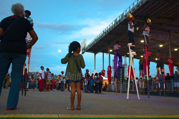 Image Caption: A child stares at the moko jumbies all around her at The Launch of Trinidad and Tobago Carnival 2019. 23rd September, 2018.