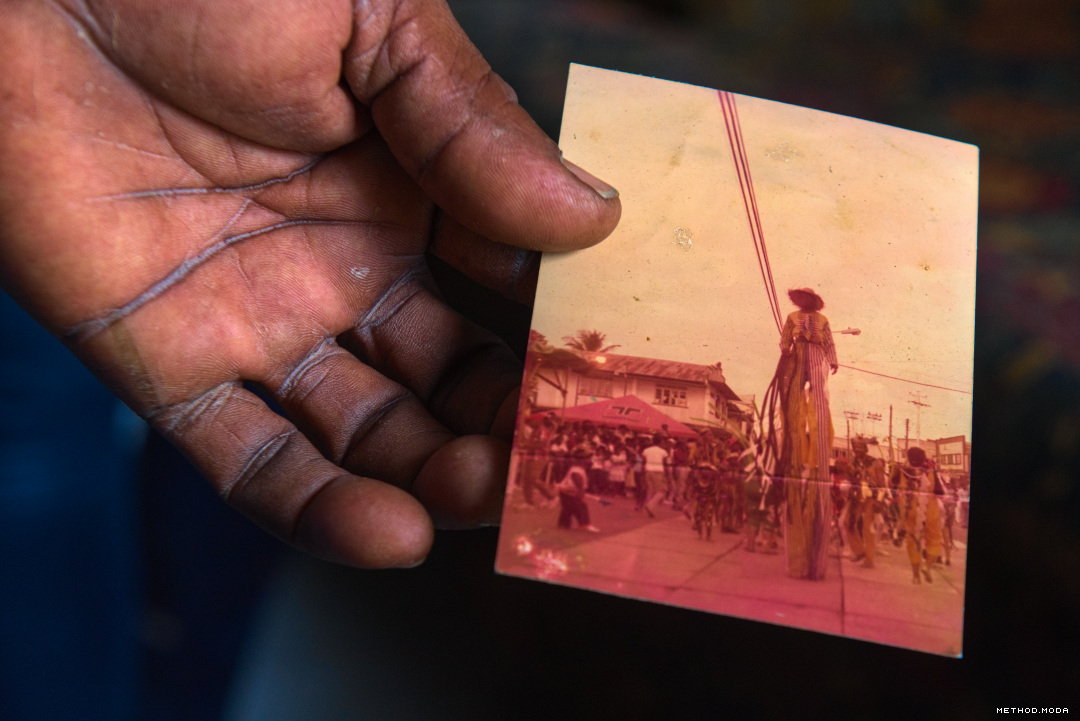 Image Caption: The hand of the enigmatic Dexter Stewart holds a photograph from his early days as a Moko Jumbie.  Hailing from Point Fortin, South Trinidad, he began walking bamboo sticks in the 1970s, using an improvised costume to take part in Children's Carnival around the age of eleven.  Later mentorship by John Cupid and Dave Robeson would then expose him to opportunity and the mythologies of Old Mas and Moko Jumbie.  Point Fortin—12th March, 2020.  #caribbean #culture #daverobeson #dexterstewart #johncupid #history #pointfortin #methodmoda #mokojumbie #stickwalker #stiltwalkers_caribbean #stiltwalkers_trinbago #stiltwalkers_worldwide #trinbago #trinidad #trinidadandtobago—Click to read this article.
